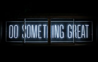 white neon sign on a black background that reads, do something great